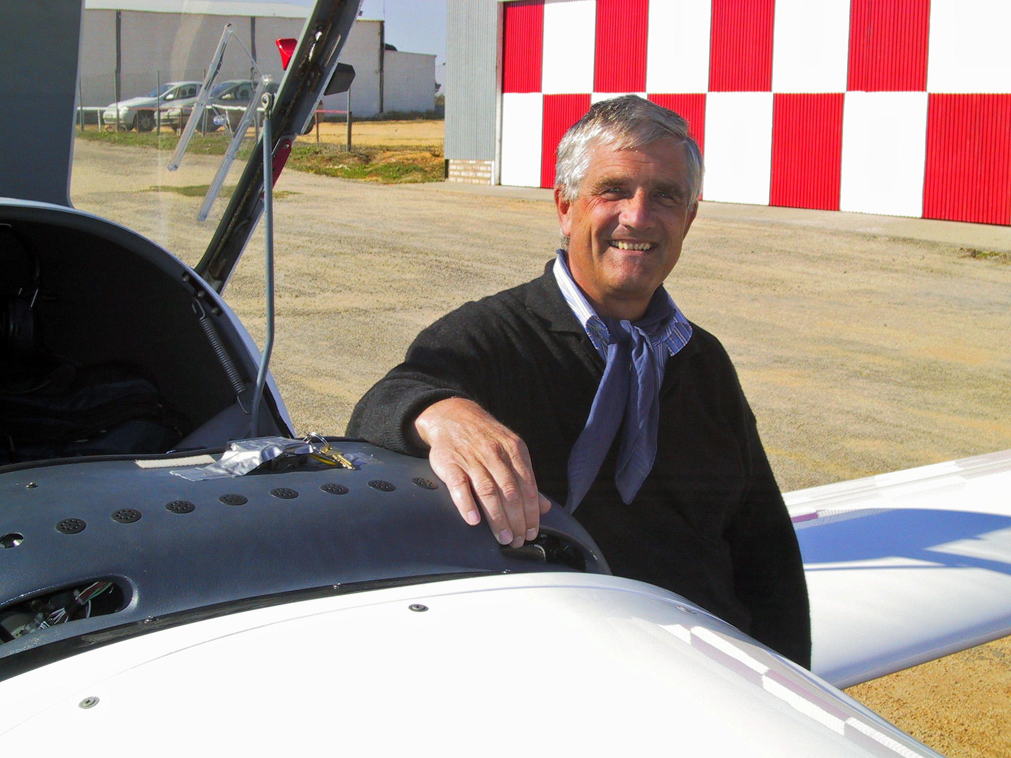 Fluglehrer steht bei Sonnenschein vor Kleinflugzeug und lächelt in die Kamera.